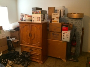 A collection of our life's possessions piled in our bare bedroom, ready to be shipped off to Guam.